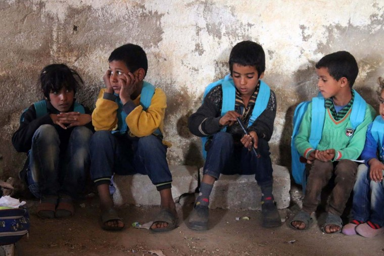 Syrian children sit on the floor in a barn that has been converted into a makeshift school to teach internally displaced children from areas under government control, in a rebel-held area of Daraa, in southern Syria on November 10, 2016. The school has a shortage of seats prompting many children to sit on stones instead. Rebels hold most of Daraa province, but the regional capital is largely controlled by the government. (MOHAMAD ABAZEED/AFP/Getty Images)
