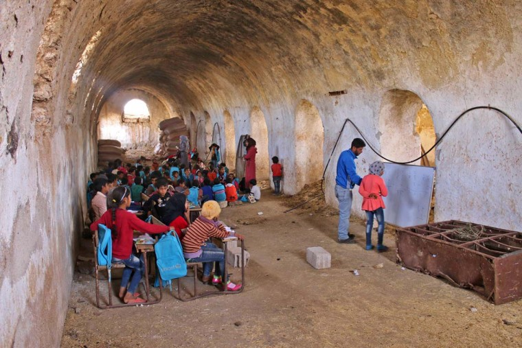 A Syrian girl practices basic arithmetic operations with a teacher during class in a barn that has been converted into a makeshift school to teach internally displaced children from areas under government control, in a rebel-held area of Daraa, in southern Syria on November 10, 2016. The school has a shortage of seats prompting many children to sit on stones instead. Rebels hold most of Daraa province, but the regional capital is largely controlled by the government. (MOHAMAD ABAZEED/AFP/Getty Images)