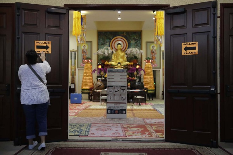 Polling volunteer Mary Roca, 51, posts signs on the door of Chua Phat To Gotama Temple before the polling place opens for voting Tuesday, Nov. 8, 2016, in Long Beach, Calif. (AP Photo/Jae C. Hong)