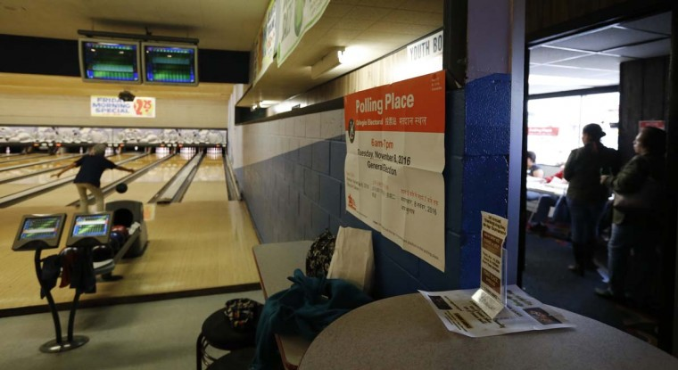 A member of the Early Bird bowling league bowls, left, as voters wait in line to cast their ballots, right, at the Lawn Lanes Bowling Alley on Tuesday, Nov. 8, 2016, in Chicago. (AP Photo/Charles Rex Arbogast)