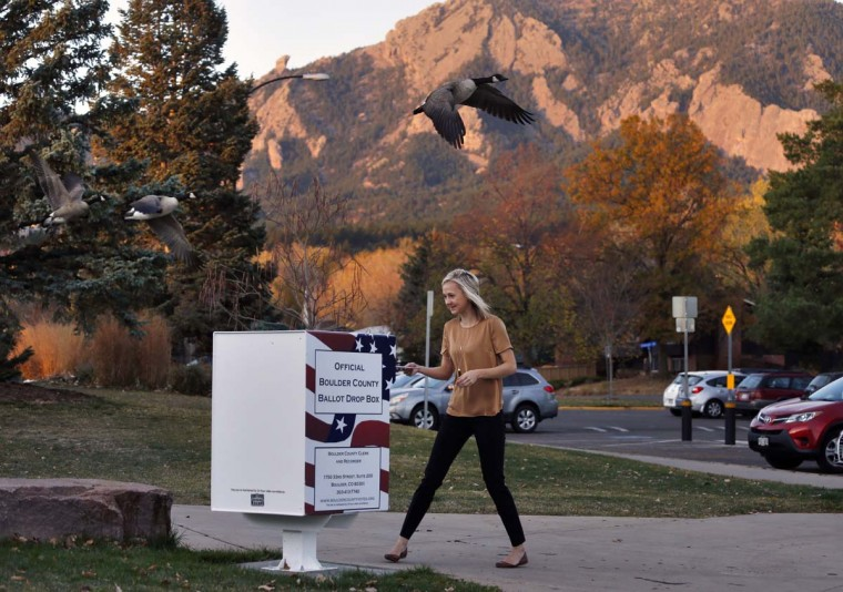 "Emily Chatburn, who teaches 3rd grade at a local elementary school, puts her completed voter ballot into a drop box at a recreation center in Boulder, Colo., Tuesday, Nov. 8, 2016. Regarding the divisiveness in American politics, Chatburn says: ""I try to get an understanding for both sides, where they are coming from… I think that it will be very interesting to see what happens. And whatever president it is, they'll get settled, and I think, just really, I'm hoping that no matter who the president is, that our other checks and balances will make sure that either president makes the right choice for our country. I believe in the fabric of our democracy too."" (AP Photo/Brennan Linsley)"