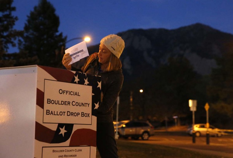 "MJ McCoy, who works as a food industry recruiter, puts her completed voter ballot into a drop box at a recreation center before dawn in Boulder, Colo., Tuesday, Nov. 8, 2016. Regarding the significance of having a woman on the ballot, McCoy, who voted for Clinton, says: ""It meant a lot to me to see that women finally have a chance to have the highest office in the country. I think it's really awesome, and it's been overshadowed by all the negativity in the campaign."" (AP Photo/Brennan Linsley)"