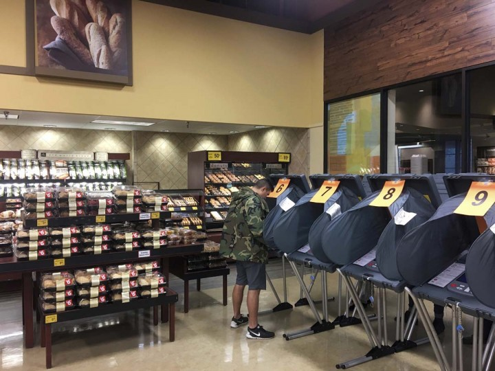 A man votes in the bakery department at a Randalls grocery store in Austin, Texas, on Tuesday, Nov. 8, 2016. (Jay Janner/Austin American-Statesman via AP)