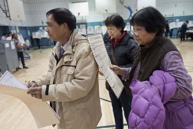 Zhou Nan Zhou, left, his wife, Li Li Tan, center, and their friend, Yulsman Yang, right, wait to cast their ballots, Tuesday, Nov. 8, 2016, in the Sunset Park neighborhood in the Brooklyn borough of New York. They are originally from China. The neighborhood is ethnically diverse, with a large Asian and Hispanic population. (AP Photo/Mark Lennihan)