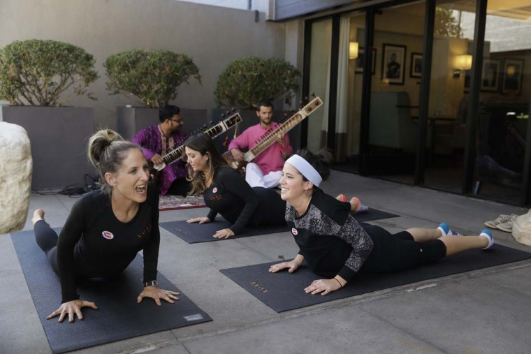Yoga instructor Rachel Jackson, left, leads a free yoga session for voters including Megan Gallagher, right, outside a polling place at Luxe Sunset Boulevard Hotel Tuesday, Nov. 8, 2016, in Los Angeles. (AP Photo/Jae C. Hong)