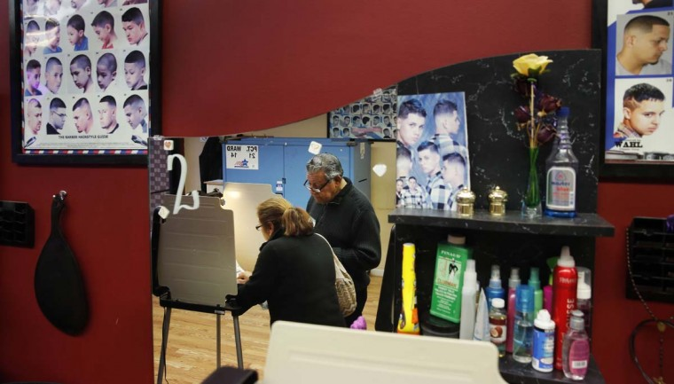 Democratic polling judge John Ramirez, right, is reflected in a mirror as he assists a voter as she fills out her ballot at Delia's Beauty Salon on Tuesday, Nov. 8, 2016, in Chicago. (AP Photo/Charles Rex Arbogast)
