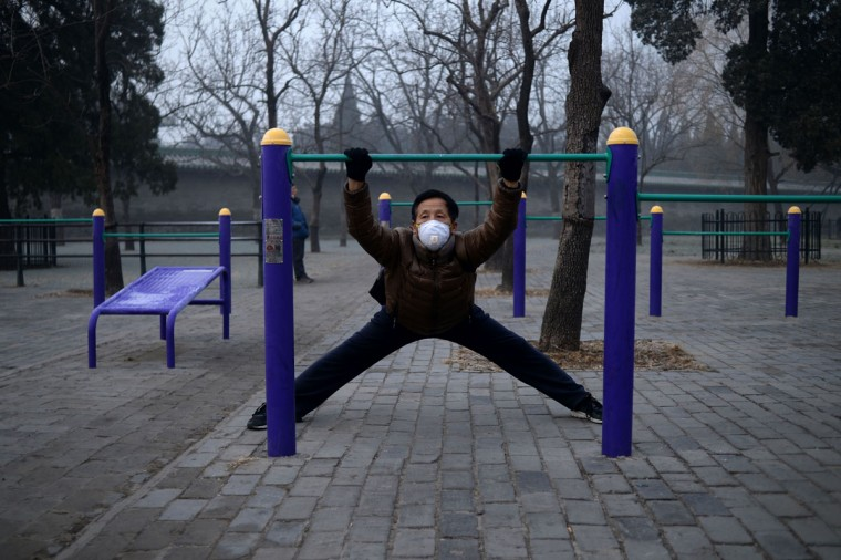 An elderly man wearing a mask exercises at a park in Beijing on December 20, 2016. Heavy smog suffocated northeast China for a fifth day on December 20, with hundreds of flights cancelled and road and rail transport grinding to a halt under the low visibility conditions. (AFP PHOTO / WANG ZHAO)