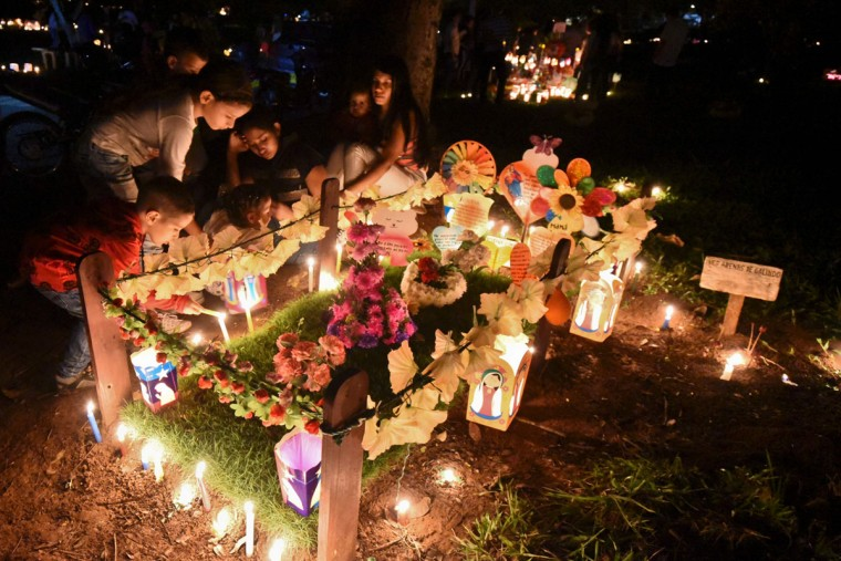 """Locals light candles at the """"Jardines de la Aurora"""" cemetery in Cali, department of Valle del Cauca, Colombia, on December 7, 2016, during the celebration of the Day of the Candles -one of the most important religious holidays in Colombia which marks the beginning of the Christmas holidays. (AFP PHOTO / LUIS ROBAYOLUIS ROBAYO/AFP/Getty Images)"""