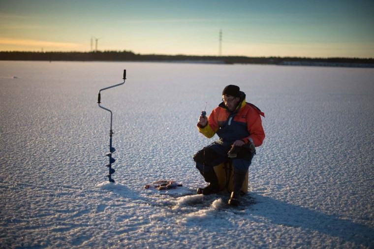 A man is ice-fishing at midday on the frozen Bothnia Sea, on December 28, 2016 in Vaasa, Western Finland. (OLIVIER MORIN/AFP/Getty Images)