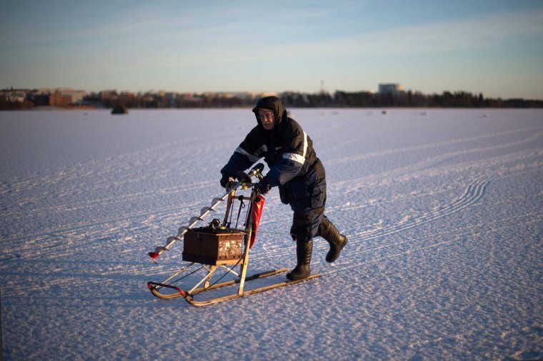 A man going ice-fishing slides on a vintage sled carrying a powerdrill and his fishing gear on the frozen Bothnia Sea, on December 28, 2016 in Vaasa, Western Finland. (OLIVIER MORIN/AFP/Getty Images)