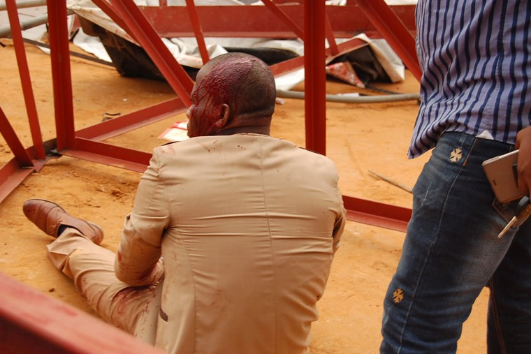 This picture taken on December 10, 2016 shows an injured man sitting amid rubble at the scene after an evangelical church roof collapsed on worshipers in the remote southeastern city of Uyo, the capital of Akwa Ibom state. The search for survivors continued after a church roof collapsed killing at least 60 people, with many more feared dead. (Stringer/AFP/Getty Images)