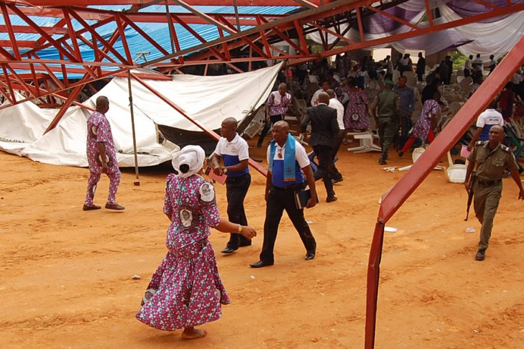 This picture taken on December 10, 2016 shows people walking through the wreckage after an evangelical church roof collapsed on worshipers in the remote southeastern city of Uyo, the capital of Akwa Ibom state. The search for survivors continued after a church roof collapsed killing at least 60 people, with many more feared dead. (Stringer/AFP/Getty Images)