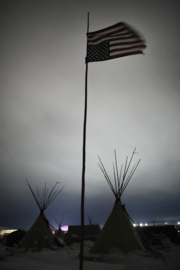 An upside down American flag flies above Oceti Sakowin Camp on the edge of the Standing Rock Sioux Reservation on November 30, 2016 outside Cannon Ball, North Dakota. A flag flown upside down is a symbol of distress. Native Americans and activists from around the country have been gathering at the camp for several months trying to halt the construction of the Dakota Access Pipeline. The proposed 1,172-mile-long pipeline would transport oil from the North Dakota Bakken region through South Dakota, Iowa and into Illinois. (Photo by Scott Olson/Getty Images)