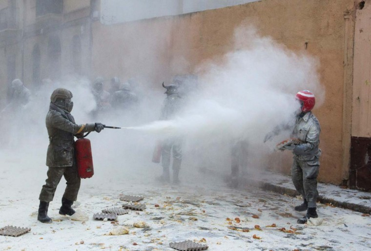 "Revellers dressed in mock military garb take part in the ""Enfarinats"" battle in the southeastern Spanish town of Ibi on December 28, 2016. During this 200-year-old traditional festival participants known as Els Enfarinats (those covered in flour) dress in military clothes and stage a mock coup d'etat as they battle using flour, eggs and firecrackers outside the city town hall as part of the celebrations of the Day of the Innocents. (JAIME REINA/AFP/Getty Images)"