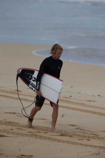 World Surfing Champion 2016 John John Florence of Hawaii walks on the beach with his surfboard on December 25, 2016 on the island of Oahu in Hawaii, following competition in Billabong Pipe Masters. Christmas Day at the pipeline was the best day of the winter season so far with huge tubes coming through great surfing rides and heavy wipeouts with the world's best surfers catching waves and dominating the pack. (Brian Bielmann/AFP/Getty Images)
