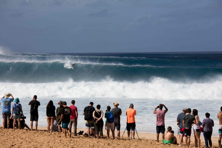 Spectators watch as Nathan Fletcher of the US rides the waves on December 25, 2016 on the island of Oahu in Hawaii, following competition in Billabong Pipe Masters. Christmas Day at the pipeline was the best day of the winter season so far with huge tubes coming through great surfing rides and heavy wipeouts with the world's best surfers catching waves and dominating the pack. (Brian Bielmann/AFP/Getty Images)