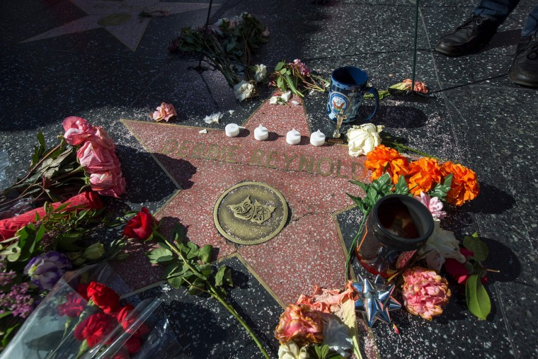 "Memorial items are left at one of the Hollywood Walk of Fame stars for actress Debbie Reynolds on December 29 in Hollywood, California. Reynolds, the ""Singin' in the Rain"" actress who tap-danced her way into American hearts as a star of Hollywood's Golden Age, died on December 28, 2016, grief-stricken over daughter Carrie Fisher's death a day earlier. (David McNew/AFP/Getty Images)"