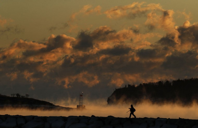 "Darryl Hendricks moves into position on a breakwater to photograph sea smoke rising off the waters of Casco Bay, Friday, Dec. 16, 2016, in South Portland, Maine. Hendricks risked both frost bite and being late for work in pursuit of what he called ""the one shot I really wanted."" The temperature dropped to minus-2 degrees Fahrenheit with a wind chill of minus-25. (AP Photo/Robert F. Bukaty)"