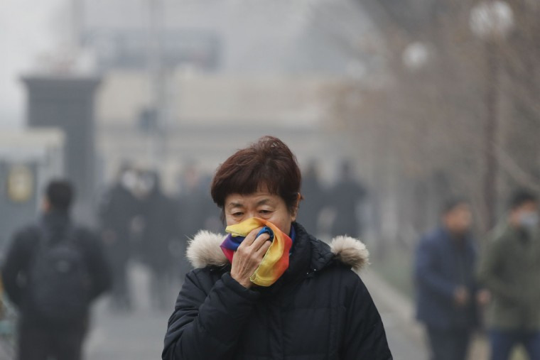 A woman uses a scarf to cover her for protection against air pollution walks on street in Beijing as the capital of China is shrouded by heavy smog on Tuesday, Dec. 20, 2016. Thick, gray smog fell over Beijing on Tuesday, choking China's capital in a haze that spurred authorities to cancel flights and close some highways in emergency measures to cut down on air pollution. (AP Photo/Andy Wong)