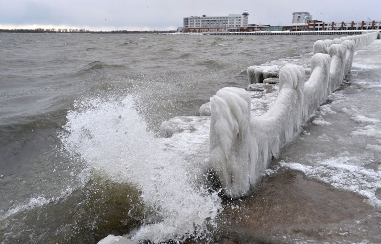 Waves crash along frozen abutments and fencing Thursday, Dec. 15, 2016 on Presque Isle Bay in Erie, Pa. Much of the northern Mid-Atlantic and Northeast will stay cold for the next couple of days as the arctic air remains stuck over the northern Appalachians, the National Weather Service said. (Christopher Millette/Erie Times-News via AP)