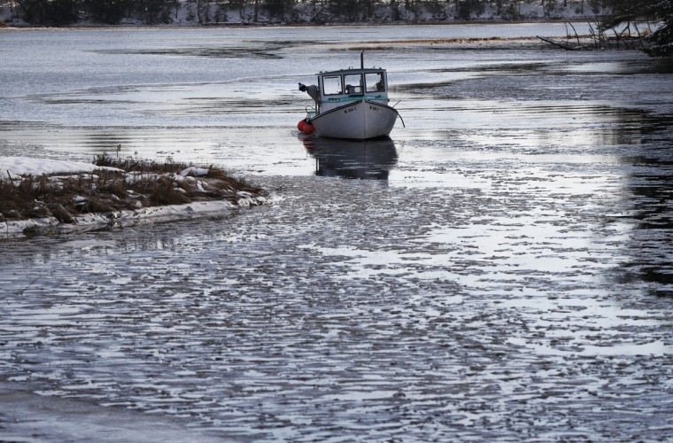 Lobsterman Jack O'Donoghue checks the icy waters of the Harraseeket River as he prepares to have his 30-foot fishing boat, the Mary Elizabeth, hauled out of the water for winter, Thursday, Dec. 15, 2016, in Freeport, Maine. Much of the northern Mid-Atlantic and Northeast will stay cold for the next couple of days as the arctic air remains stuck over the northern Appalachians, the National Weather Service said. (AP Photo/Robert F. Bukaty)