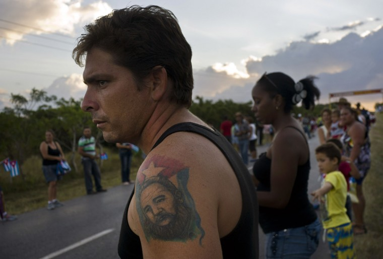 In this Nov. 30, 2016 photo, a man with a tattoo of Cuba'a late leader Fidel Castro, waits for the arrival of the caravan carrying his ashes during a funeral procession that retraces the path of Castro's triumphant march into Havana nearly six decades ago, in Cruces, Cuba. Castro's ashes completed in Santa Clara the first leg of a cross-country trip, a four-day journey across Cuba from Havana to their final resting place in the eastern city of Santiago. (AP Photo/Ramon Espinosa)