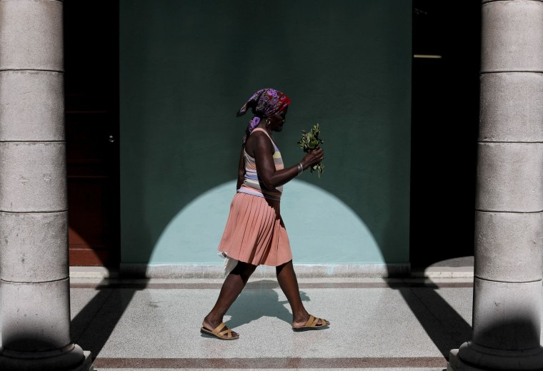 In this Nov. 29, 2016 photo, a woman arrives at a memorial in honor of late Cuban leader Fidel Castro, holding a bouquet of flowers, in Guanabacoa on the outskirts in Havana, Cuba. President Raul Castro said Cuba would bars statues of Castro and monuments bearing his name in keeping with the former leader's desire to prevent the growth of a cult of personality. (AP Photo/Natacha Pisarenko)