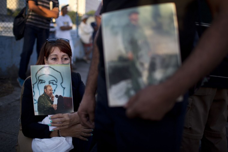 In this Nov. 28, 2016 photo, a woman holds an image of the late Cuban leader Fidel Castro, as she waits in line to pay her final respects, in Havana, Cuba. Thousands of Cubans lined up early for the start of week-long services bidding farewell to the man who ruled the country for nearly half a century. (AP Photo/Rodrigo Abd)