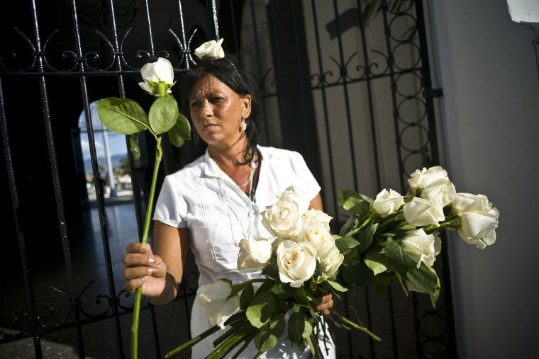 A woman hands over rose to people visiting the tomb of Cuba's leader Fidel Castro at the Santa Ifigenia cemetery in Santiago, Cuba, Saturday, Dec. 3, 2016. A wooden box containing Fidel Castro's ashes was placed by his brother and successor Raul on Sunday into the side of a granite boulder that has become Cuba's only official monument to the charismatic bearded rebel. (AP Photo/Ramon Espinosa)