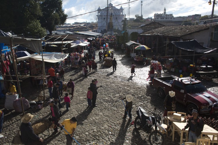 Vendors set up early in the morning during a week-long celebration honoring Saint Thomas, the patron saint of Chichicastenango, Guatemala, Wednesday, Dec. 21, 2016. The Feast of Saint Thomas draws international tourists with its colorful pageantry, but at its heart is a religious celebration melding Catholic and indigenous traditions that culminates on Dec. 21. (AP Photo/Moises Castillo)