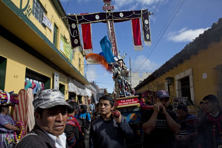 Men carry a religious statue during a procession in honor of Saint Thomas, the patron saint of Chichicastenango, Guatemala, Wednesday, Dec. 21, 2016. The statue is the symbol of one of the town's Catholic brotherhoods, represented by a cross and statue of Jesus. (AP Photo/Moises Castillo)