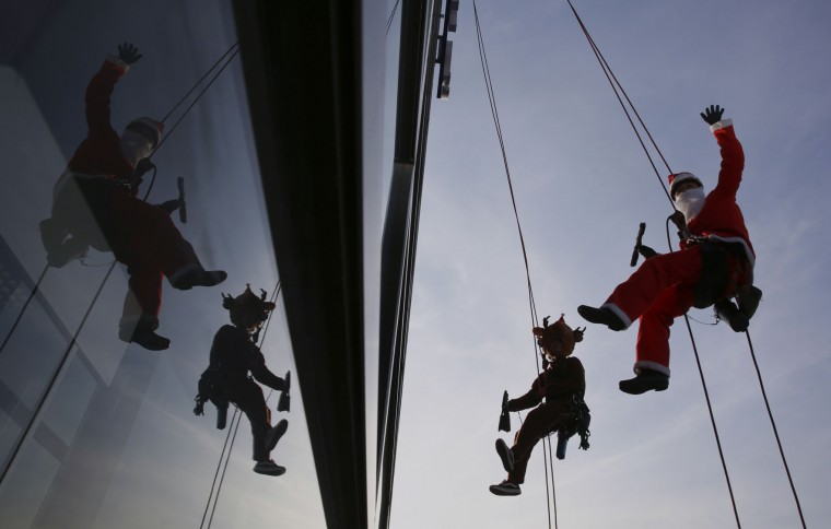 Window cleaners dressed as Santa Claus and reindeer pose for photographers while cleaning windows at a shopping mall in Tokyo's Daiba bay area, Wednesday, Dec. 21, 2016. (AP Photo/Eugene Hoshiko)
