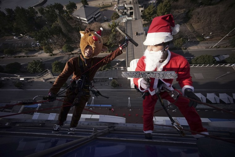 Window cleaners dressed as Santa Claus and a reindeer pose for photographers while cleaning windows at a shopping mall in Tokyo's Daiba bay area, Wednesday, Dec. 21, 2016. (AP Photo/Eugene Hoshiko)
