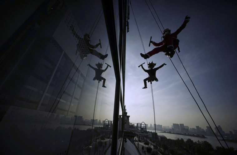 Window washers dressed as Santa Claus and a reindeer clean windows at a shopping mall in Tokyo's Daiba bay area, Wednesday, Dec. 21, 2016. (AP Photo/Eugene Hoshiko)