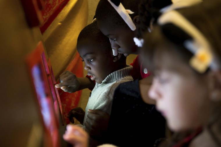 "In this Sunday, Nov. 20, 2016, photo, Brandon Mack, 13, second from left, helps his younger brother Jordan Mack, 4, left, make a greeting card on an iPad inside the ""Adventure to Santa,"" a DreamWorks DreamPlace experience at North Point Mall, in Alpharetta, Ga. (AP Photo/Branden Camp)"