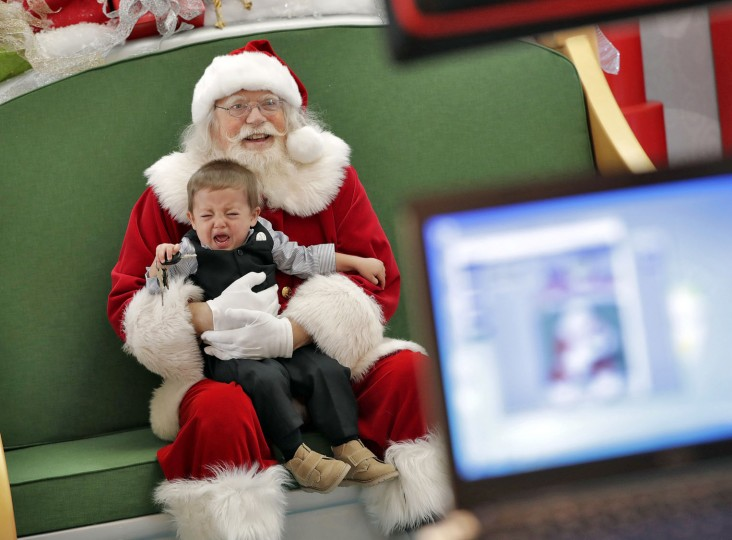 In this Thursday, Nov. 17, 2016, photo, a child has his photo taken with Santa Roger Edmonds at the Santa HQ at the Chandler Mall, in Chandler, Ariz. The Santa experience has gotten a makeover as many malls install shows and games they hope will lure shoppers who are buying more online. (AP Photo/Matt York)