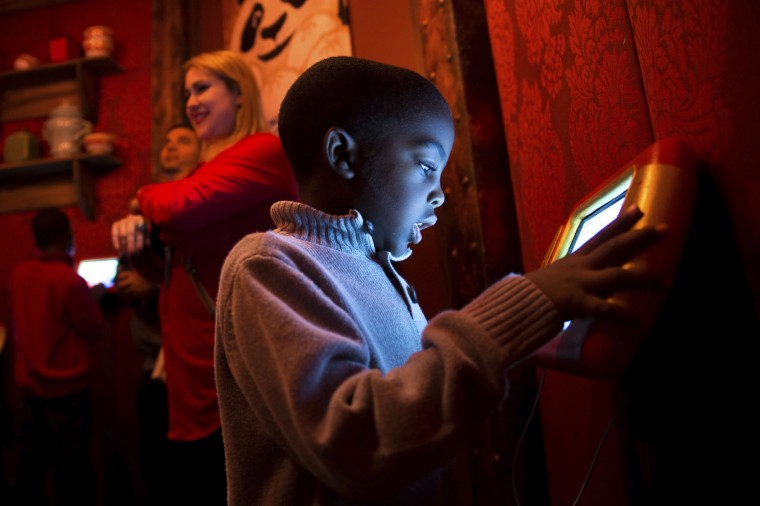 "In this Sunday, Nov. 20, 2016, photo, Jordan Mack, 4, plays on an iPad inside the ""Adventure to Santa,"" a DreamWorks DreamPlace experience at North Point Mall, in Alpharetta, Ga. (AP Photo/Branden Camp)"