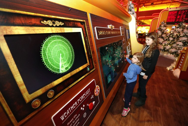 In this Monday, Nov. 21, 2016, photo, Liliana Santia, 5, and her sister Natalia, 9, check on Santa's route at Santa's Flight Academy in Great Lakes Crossing Outlets in Auburn Hills, Mich. In an effort to lure online shoppers to their stores, many malls are upgrading the traditional visit to Santa into a high-tech experience. (AP Photo/Paul Sancya)