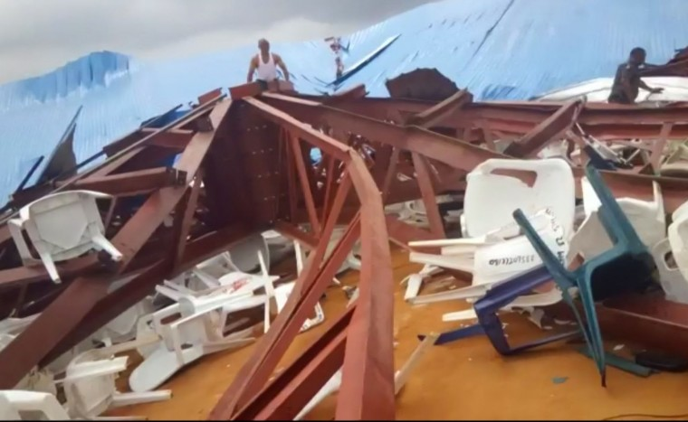 In this image made from video taken on Saturday, Dec. 10, 2016, local people survey the scene after a church roof collapsed in Uyo, Nigeria. Metal girders and the roof of a crowded church collapsed onto worshipers in southern Nigeria, killing at least 160 people with the toll likely to rise, a hospital director said Sunday. Mortuaries in the city of Uyo are overflowing from Saturday's tragedy, medical director Etete Peters of the University of Uyo Teaching Hospital told The Associated Press. (Ukeme Eyibio via AP)
