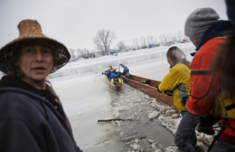 In this Thursday, Dec. 1, 2016 photo, a canoe carrying members of the Colville Native American tribe are pulled into shore upon arriving at the Oceti Sakowin camp where people have gathered to protest the Dakota Access oil pipeline in Cannon Ball, N.D. They traveled from Montana with fellow tribal members on canoe for 10 days down the Missouri river to reach the camp. (AP Photo/David Goldman)