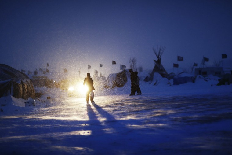 In this Tuesday, Nov. 29, 2016 photo, a person walks through a snow storm at the Oceti Sakowin camp where people have gathered to protest the Dakota Access oil pipeline in Cannon Ball, N.D. Those in the camp have shrugged off the heavy snow, icy winds and frigid temperatures. But if they defy next week's government deadline to abandon the camp, demonstrators know the real deep freeze lies ahead. (AP Photo/David Goldman)