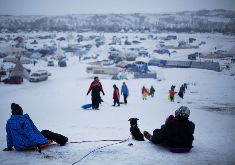 In this Thursday Dec. 1, 2016 photo, the Oceti Sakowin camp where people have gathered to protest the Dakota Access oil pipeline stands in the background as a children sled down a hill in Cannon Ball, N.D. The government has ordered protesters to leave federal land by Monday, but they insist they will stay for as long it takes to divert the $3.8 billion pipeline. (AP Photo/David Goldman)