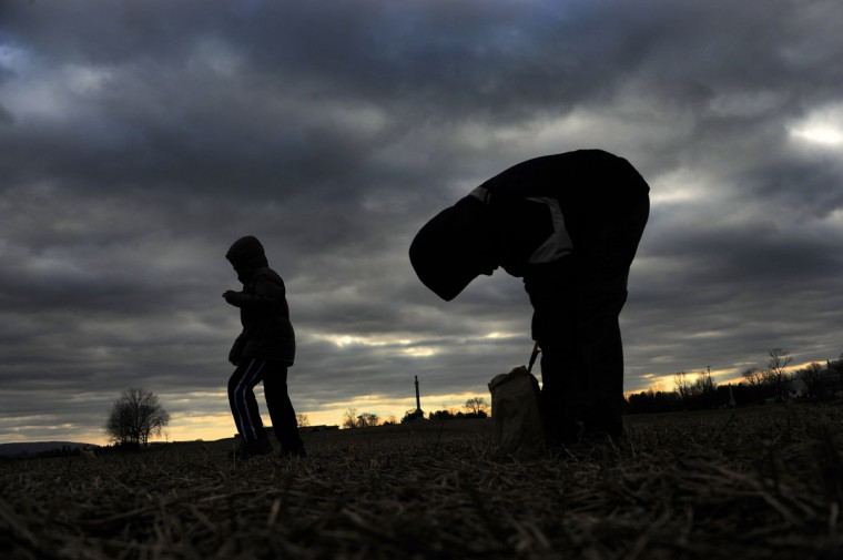 Young volunteers with Boy Scout Troop 233 of Bethesda, Md. are silhouetted against a gray sky as they light luminaries on the field near Smoketown Road during the 28th Annual Memorial Illumination of over 23,000 luminaries at Antietam National Battlefield. (Karl Merton Ferron/Baltimore Sun)