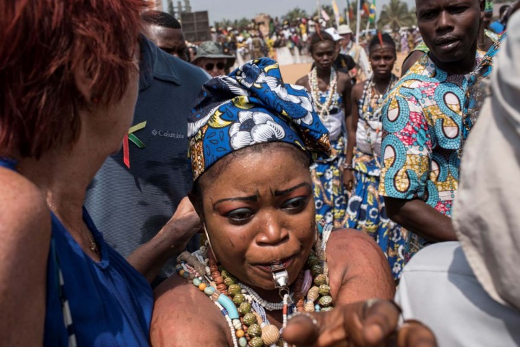 A Voodoo devotee blows a whistle as she tries to make her way through the large crowd of devotees and tourists attending the annual Voodoo Festival on January 10, 2017 in Ouidah. (STEFAN HEUNIS/AFP/Getty Images)