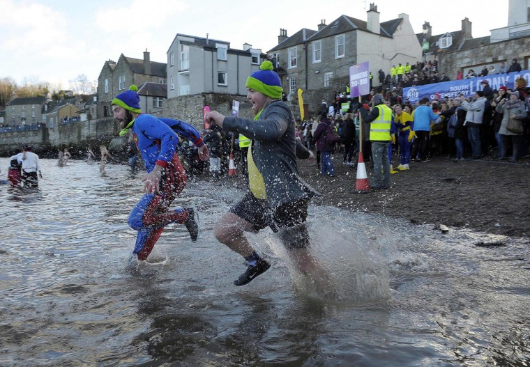 "Participants take part in the annual New Year's Day ""Loony Dook"" swim, in the Firth of Forth, in South Queensferry, near Edinburgh, on January 1, 2017. Every year people brave the River Forth, near the Forth Bridge, on New Year's Day to see in the New Year and raise money for charity. (AFP PHOTO / Andy Buchanan)"