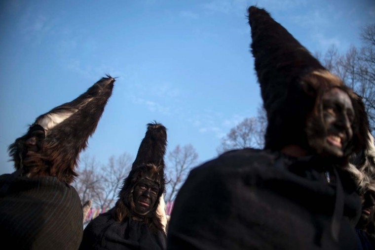 """Dancers, known as """"Kukeri"""", perform on January 29, 2017 during the International Festival of the Masquerade Games in Pernik, near the capital Sofia. The three-day festival, which started on January 27, has participants sporting multi-colored masks, covered with beads, ribbons and woolen tassels while the main dancer, ladened with bells to drive away sickness and evil spirits, sways like a wheat spikelet heavy with grain. (NIKOLAY DOYCHINOV/AFP/Getty Images)"""