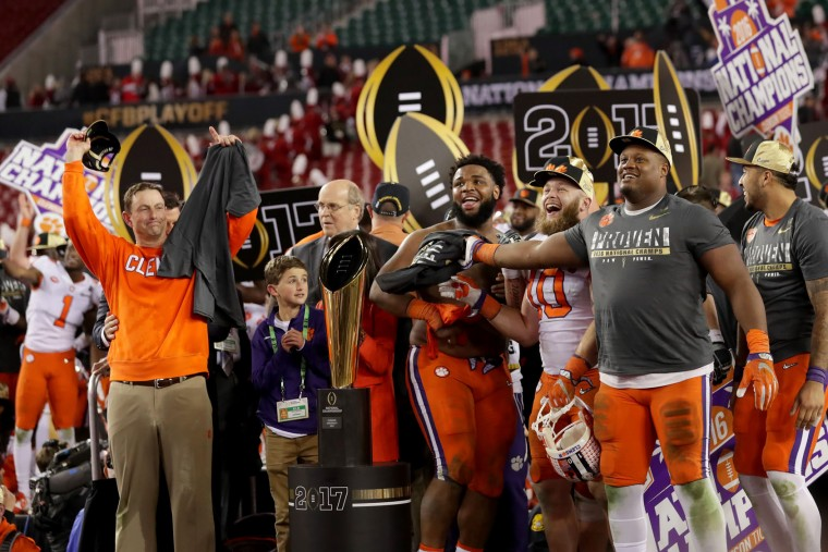 Head coach Dabo Swinney of the Clemson Tigers (L) and defensive tackle Carlos Watkins #94 (C) react after defeating the Alabama Crimson Tide 35-31 to win the 2017 College Football Playoff National Championship Game at Raymond James Stadium on January 9, 2017 in Tampa, Florida. (Photo by Streeter Lecka/Getty Images)