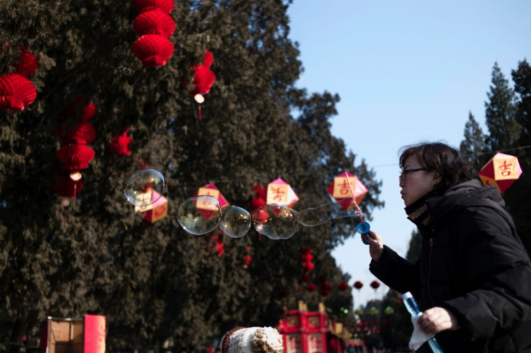 A Chinese woman blows bubbles near a tree decorated with lanterns ahead of the Lunar New Year in Beijing on January 24, 2017. The Lunar New Year, known locally as the Spring Festival, falls on January 28 this year and marks the Year of the Rooster in the Chinese calendar. (Fred Dufour/AFP/Getty Images)