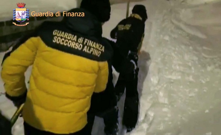 This image grab made from a video handout released by the Guardia di Finanza on January 19, 2017 shows Alpine policemen escorting a man outside the Hotel Rigopiano, near the village of Farinfola, on the eastern lower slopes of the Gran Sasso mountain. Up to 30 people were feared to have died after an Italian mountain Hotel Rigopiano was engulfed by a powerful avalanche in the earthquake-ravaged center of the country. Italy's Civil Protection agency confirmed the Hotel Rigopiano had been engulfed by a (six-feet) high wall of snow and that emergency services were struggling to get ambulances and diggers to the site. (AFP PHOTO / Guardia di Finanza press office / Handout)