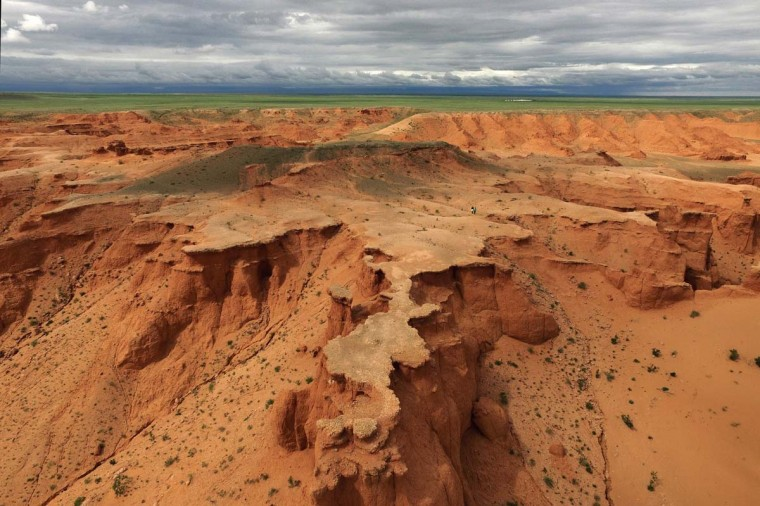 This aerial picture taken on June 27, 2016 shows two tourists on the Flaming Cliffs in the Gobi desert. For years, herder Gelegrash had a sideline bringing tourists to see a dinosaur skull hidden near the Flaming Cliffs in Mongolia's Gobi desert. Then, one day, it was gone. It is one of thousands of ancient fossils that have disappeared from the country since American explorer Roy Chapman Andrews -- supposedly the inspiration for the movie character Indiana Jones -- discovered dinosaur eggs there nearly a century ago. (JOHANNES EISELE/AFP/Getty Images)